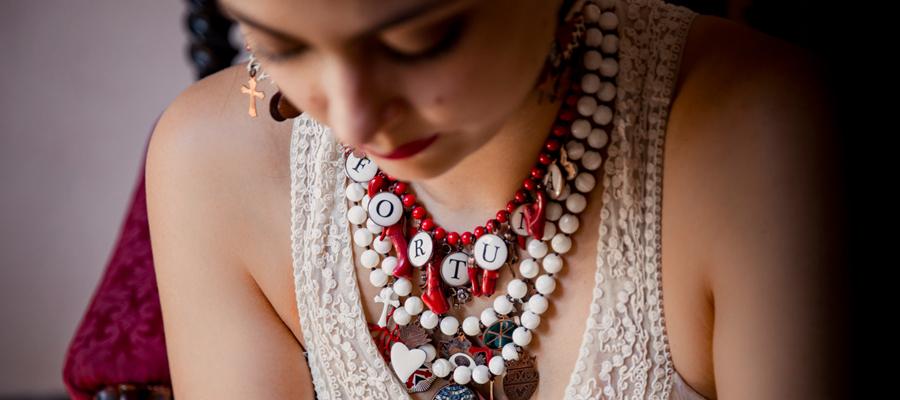 Amuleti, portafortuna, talismani corrono sulle perle in bamboo rosso corallo. Tutta la simbologia, dai cornetti ai quadrifogli, per augurare ogni bene